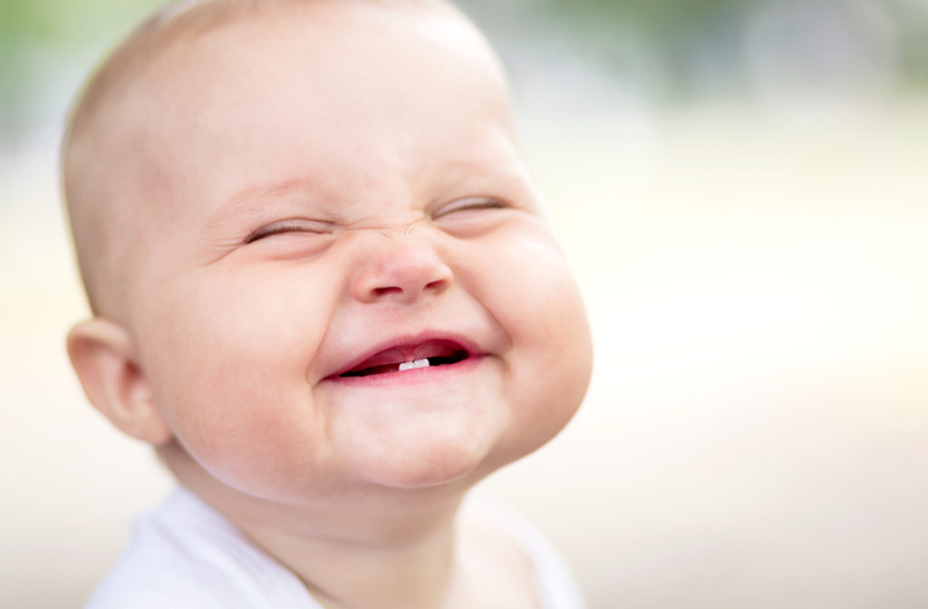 Adorable smiling baby with 2 front teeth and a gummy smile.