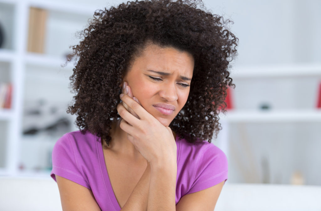 Young adult touching jaw because of wisdom tooth pain