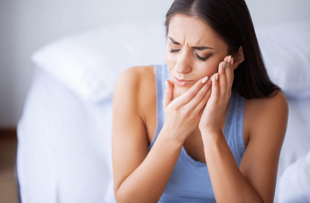 Woman with a toothache touching her jaw in pain