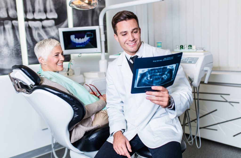 Dentist looking at x-ray of patients tooth as she sits on chair beside him