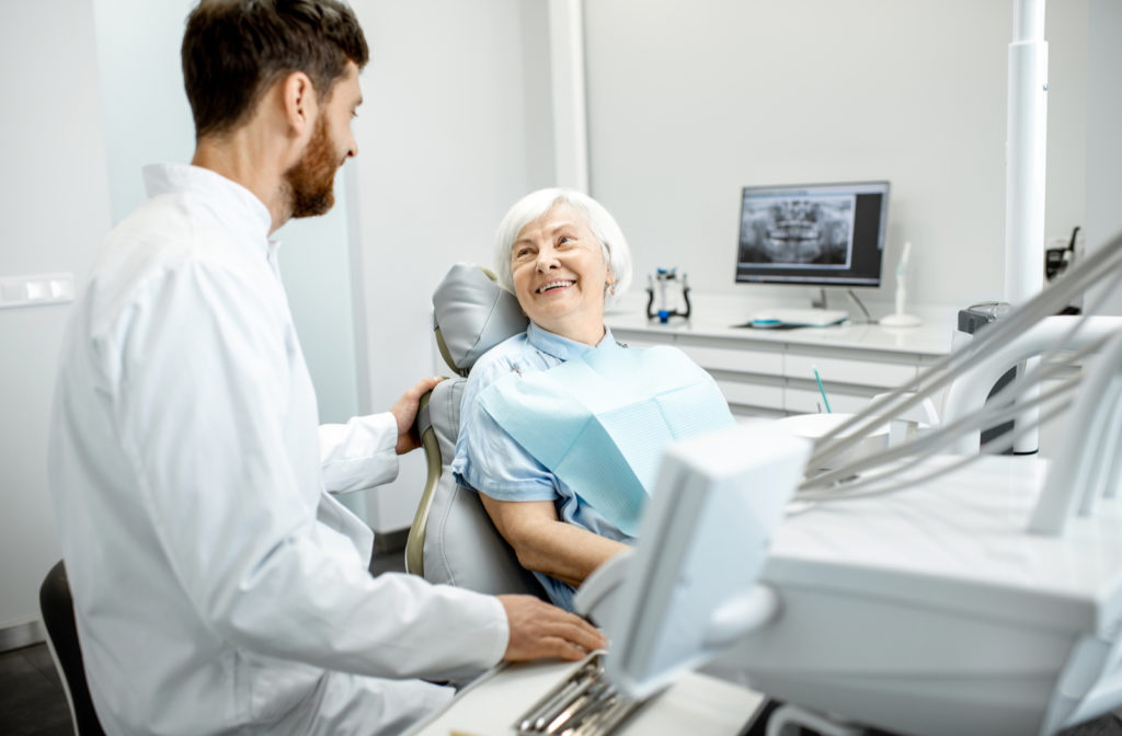 Dentist talking to happy elder patient during her dental exam consulting about dental implants